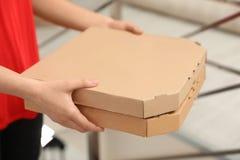 Vrouwelijke koerier met pizzadozen binnen, close-up royalty-vrije stock foto