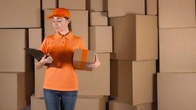 Vrouwelijke koerier in oranje eenvormig leverend een pakket aan verkeerd adres Fout of onnauwkeurigheidsconcept, 4K schot stock footage