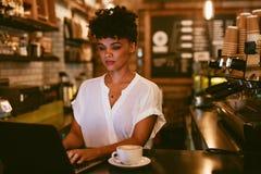 Vrouwelijke koffieeigenaar die laptop met behulp van royalty-vrije stock foto's