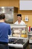 Vrouwelijke kok die op een student wacht om voedsel te kiezen Royalty-vrije Stock Foto's
