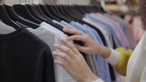 Vrouwelijke koper die voor kleren winkelen stock video