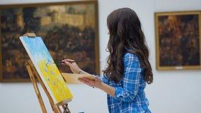 Vrouwelijke kunstenaar die een beeld op canvas schilderen Kunstgalerieachtergrond 4K stock videobeelden