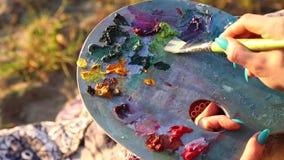 Vrouwelijke kunstenaar die het openluchtmes van het close-uppalet schilderen stock footage
