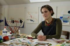 Vrouwelijke kunstenaar in haar studio met haar kunstwerk royalty-vrije stock fotografie
