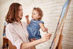 Vrouwelijke Kunstenaar Painting In Art Studio met Weinig Kind royalty-vrije stock fotografie