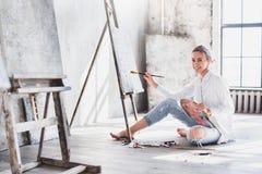Vrouwelijke Kunstenaar Working On Painting in Heldere Daglichtstudio royalty-vrije stock foto