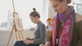 Vrouwelijke kunstenaars die artistiek etude witn naakt model in een stidio uitvoeren stock video