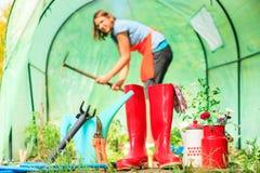 Vrouwelijke landbouwer en het tuinieren hulpmiddelen in tuin Stock Foto