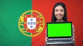 Vrouwelijke laptop van de studentenholding met het groene scherm, Portugese vlag op achtergrond stock footage