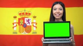 Vrouwelijke laptop van de studentenholding met het groene scherm, Spaanse vlag op achtergrond stock videobeelden