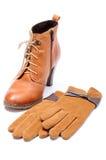 Vrouwelijke leerschoenen en handschoenen op witte achtergrond Stock Foto