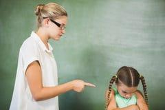 Vrouwelijke leraar die bij meisje in klaslokaal schreeuwen Stock Foto's