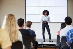 Vrouwelijke Leraar With Digital Tablet die Presentatie geven aan Middelbare schoolklasse in Front Of Screen stock foto's