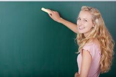 Vrouwelijke Leraar Writing On Chalkboard terwijl het Kijken over Schouder stock foto