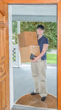 Vrouwelijke leveringspersoon in deuropening met dozen Stock Afbeelding