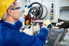 Vrouwelijke machineexploitant die bij fabriek werken stock afbeelding
