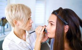 Vrouwelijke make-upkunstenaar die professionele make-up voor jonge donkerbruine vrouw doen bij schoonheidssalon royalty-vrije stock foto