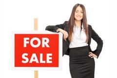 Vrouwelijke makelaar in onroerend goed die op a voor verkoopteken leunen Stock Afbeeldingen