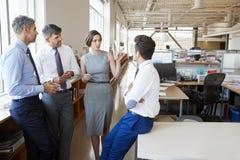 Vrouwelijke manager die aan collega's in een open planbureau spreken royalty-vrije stock foto