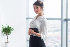 Vrouwelijke manager die bureaukostuum dragen, die houdend tablet in haar handen, die camera bekijken bevinden zich royalty-vrije stock afbeeldingen