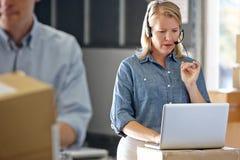 Vrouwelijke Manager die Hoofdtelefoon in het Pakhuis van de Distributie met behulp van royalty-vrije stock afbeelding