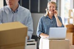 Vrouwelijke Manager die Hoofdtelefoon in het Pakhuis van de Distributie met behulp van stock afbeelding