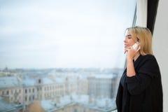 Vrouwelijke manager die met cellphonezitting roepen in bureau met draagbaar netto-boek stock afbeelding