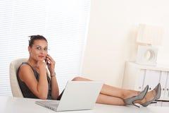 Vrouwelijke manager die met omhoog benen werkt royalty-vrije stock afbeelding