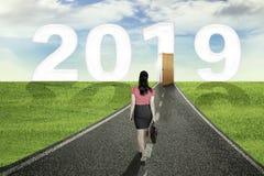Vrouwelijke managergangen aan deur en nummer 2019 stock foto's