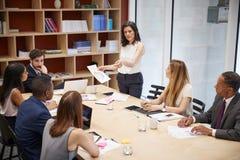 Vrouwelijke managertribunes met document op bestuurskamervergadering stock afbeelding