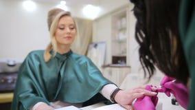 Vrouwelijke manicure die manicure doet Spijkerschoonheidsspecialist die tot manicure maken aan meisje in spijkersalon stock video