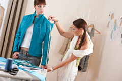 Vrouwelijke manierontwerper die jasje op model meet Stock Foto's
