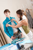 Vrouwelijke manierontwerper die jasje op model meet Stock Afbeelding