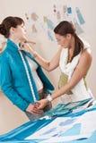 Vrouwelijke manierontwerper die jasje op model meet Stock Afbeeldingen