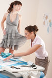 Vrouwelijke manierontwerper die kleding op model probeert Stock Foto's