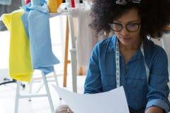 Vrouwelijke manierontwerper die schets bekijken stock foto