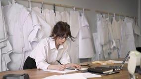 Vrouwelijke manierontwerper nota's maken die leunend op de lijst stock video