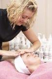 Vrouwelijke masseuse die cliënt geeft gezichts stock foto's