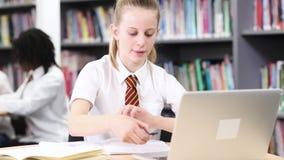 Vrouwelijke middelbare schoolstudent die het eenvormige werken dragen bij laptop stock videobeelden