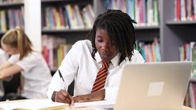 Vrouwelijke middelbare schoolstudent die het eenvormige werken dragen bij laptop stock video