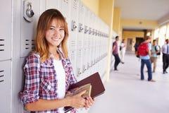 Vrouwelijke Middelbare schoolstudent Standing By Lockers Stock Afbeelding