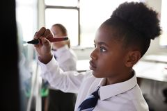 Vrouwelijke Middelbare schoolstudenten die het Eenvormige Gebruiken Interactieve Whiteboard dragen tijdens Les stock afbeeldingen