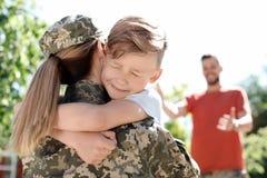 Vrouwelijke militair met haar zoon in openlucht Legerdienst stock foto's