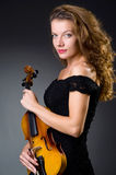 Vrouwelijke muzikale speler tegen donkere achtergrond Royalty-vrije Stock Afbeeldingen