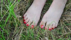 Vrouwelijke naakte benen met rode pedicure op gras stock videobeelden