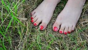 Vrouwelijke naakte benen met rode pedicure op gras stock footage
