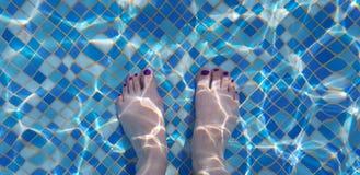 Vrouwelijke naakte die voeten door blauwe wateren van een zwembad worden gezien royalty-vrije stock afbeeldingen