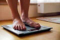 Vrouwelijke naakte voeten met gewichtsschaal stock foto