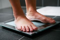 Vrouwelijke naakte voeten op de digitale schaal stock foto's