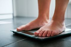 Vrouwelijke naakte voeten op de digitale schaal stock foto